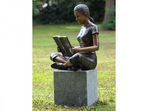 Junge Frau Margret ließt ein Buch sitzend als Bronzeskulptur