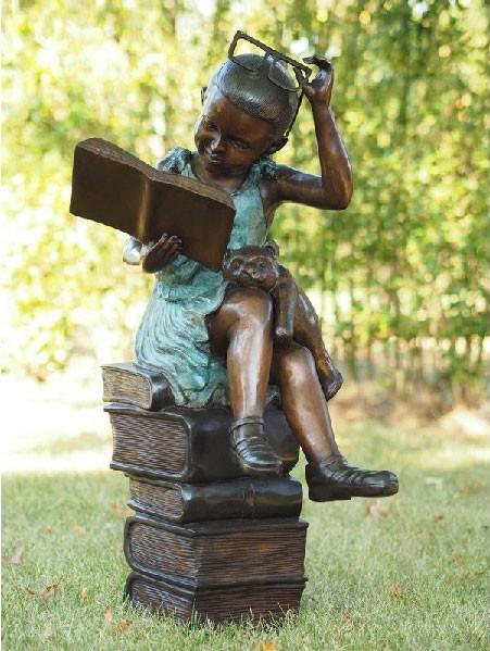 Lesend Mädchen Lara mit Brille auf ein Stapel Bücher sitzend als Bronzeskulptur