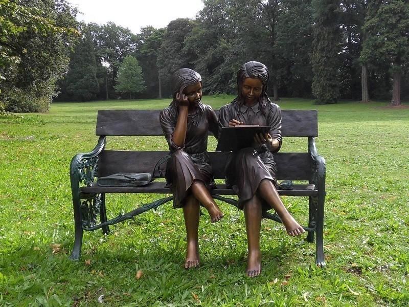 Zwei Mädchen auf einer Bank als Bronzeskulptur