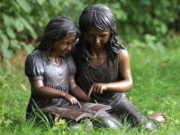 Zwei Mädchen schauen sich ein Buch gemeinsam an als Bronzeskulptur