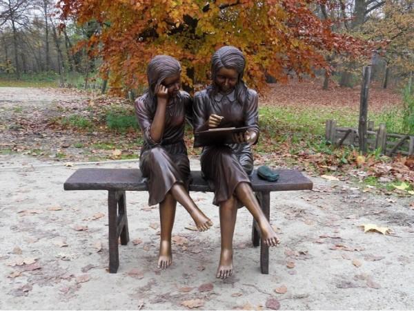Zwei Mädchen Lesend auf einer Bank als Bronzefigur