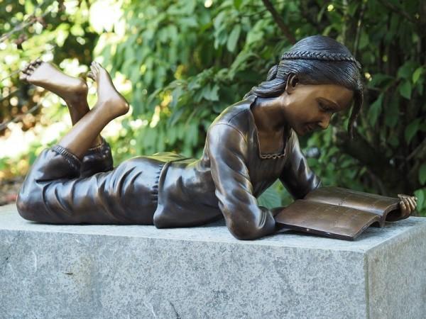 Mädchen Hilde liest Buch liegend als Bronzeskulptur