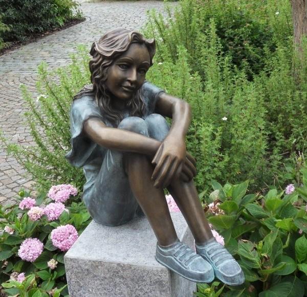 Das Mädchen Cora sitzt auf dem Boden nachdenklich als Bronzeskulptur