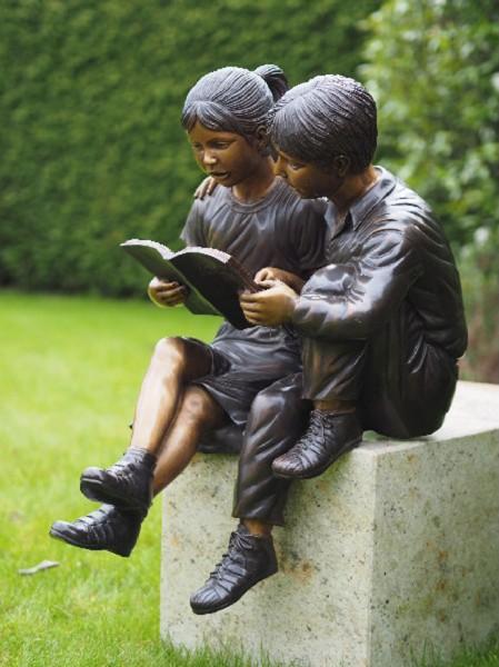 Geschwisterpaar liest zusammen ein Buch als Bronzeskulptur