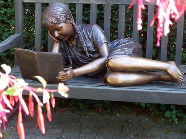 Junges Mädchen Mira liest ein Buch auf der Seite liegend als Bronzeskulptur