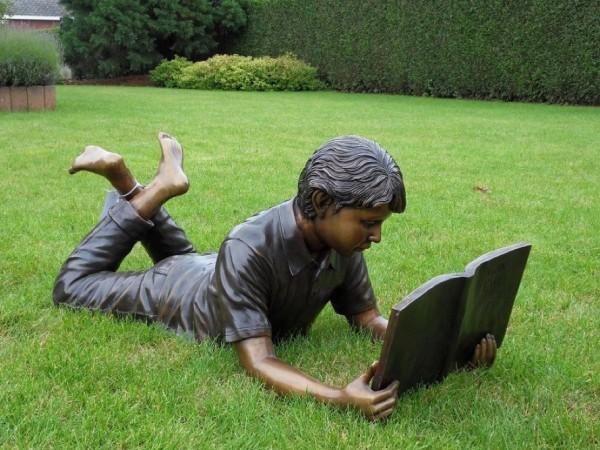 Junge Fredrick liest Buch liegend als Bronzeskulptur