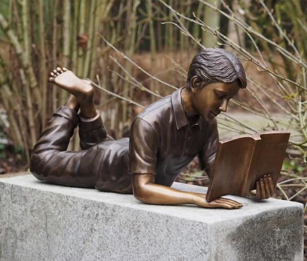 Marcel ließt ein Buch im liegen als Bronzeskulptur