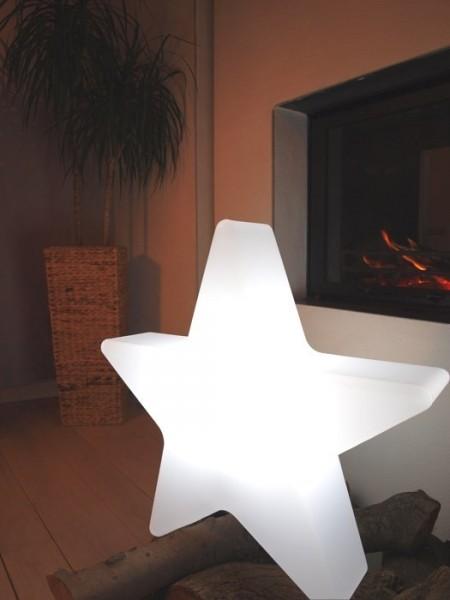 Die Windlichter als Lichtquelle besitzen ein modernes, farbiges Gestell